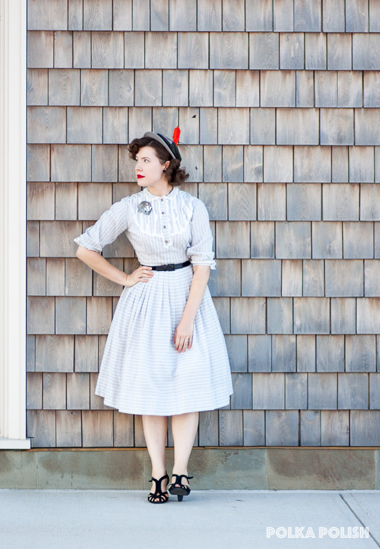 Gold and grey 1950s day dress paired with black shoes and a grey hat with orange and black feathers