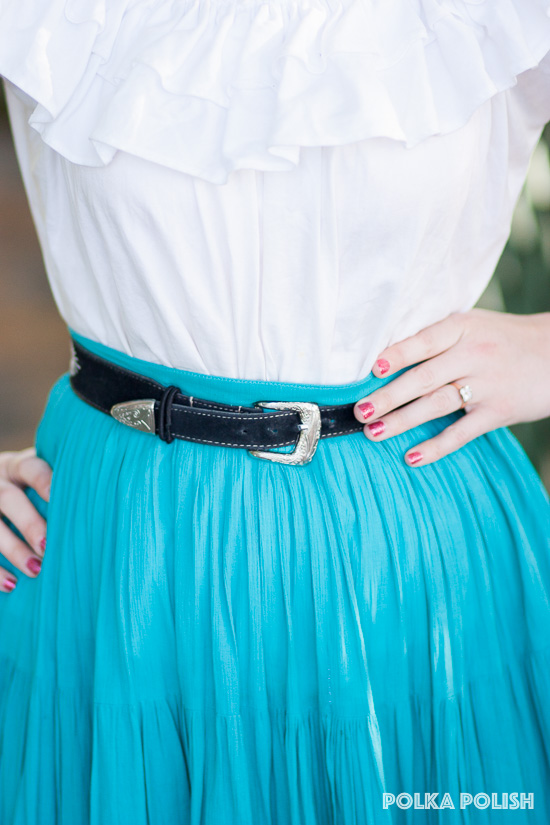 A vintage black suede belt with a stamped sliver tone buckle adds a pop of contrast to this blue and white southwestern-inspired ensemble
