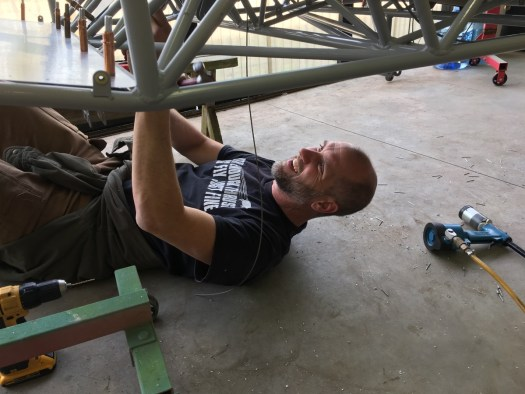 Dan laying under the plane working on something
