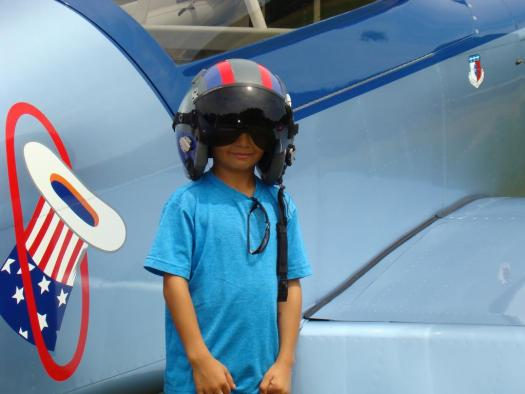 Kid wearing a flight helmet, in front of the Bandits airplane