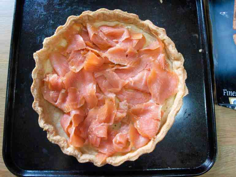 Place the smoked salmon in the base of the blind baked tart