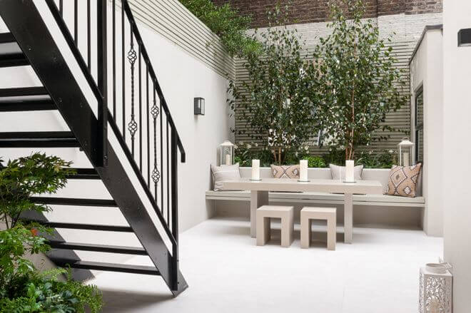 Consider built-ins. Obviously, space is at a premium with a small patio. In this modest courtyard, the raised garden bed serves as the back of a built-in bench. This adds room for a generously sized table in the space. Tall trees and slatted trellis walls keep the building walls around the courtyard from feeling oppressive.