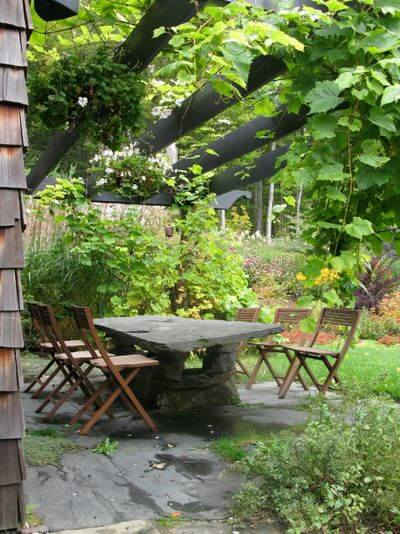 This large stone slab table coordinates with the surface underfoot, making it look as though it emerged from a rock ledge.