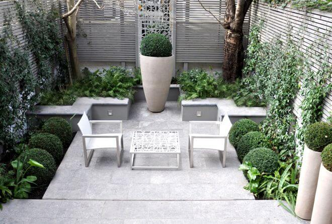 You may think you should put only small things on a small patio, but that's not the case. Look how well this oversized urn creates a focal point on this modest-sized patio. Another clever trick here: The raised bed walls serve as extra seating.