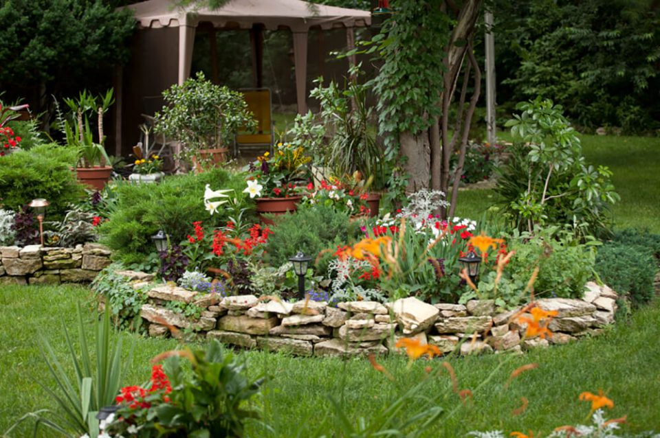 The stacked stone wall adds a rustic, homey quality to the landscaping