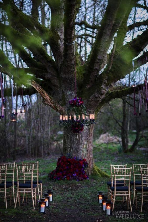 Moody florals on the tree and chandelier make the ceremony spot chic | Halloween Wedding Theme Ideas - Farmfoodfamily.com