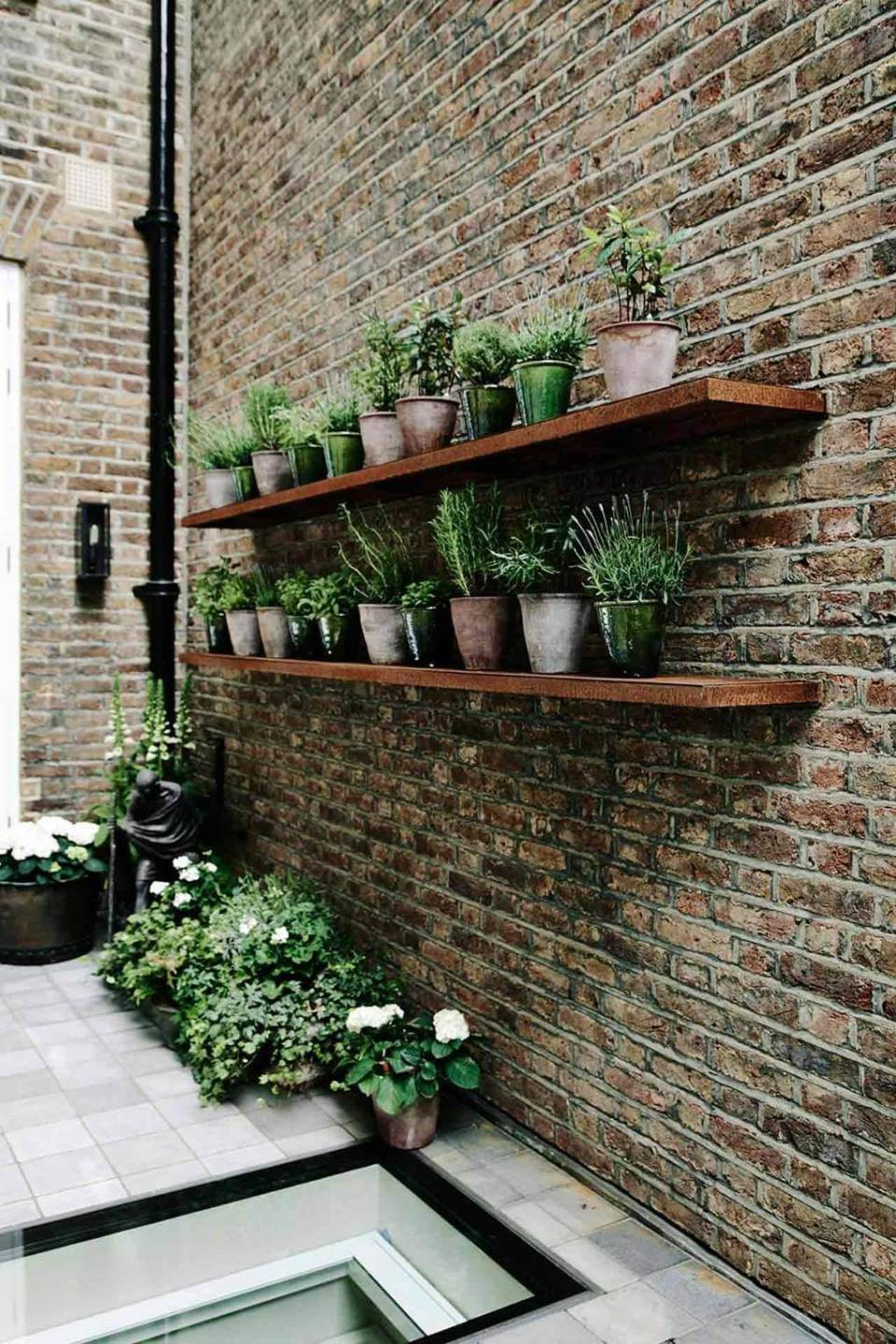 The garden terrace with potted herbs on rusted shelves