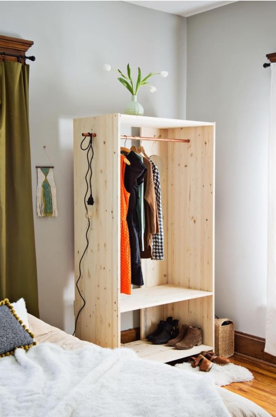 Wooden wardrobe without doors next to a bed, inside a white room