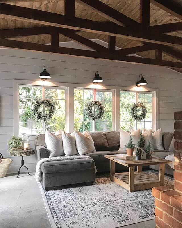 Large room with exposed beams, the windows with light fixtures and wreaths