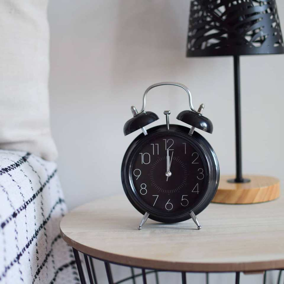 Black awakened clock on the bedside table