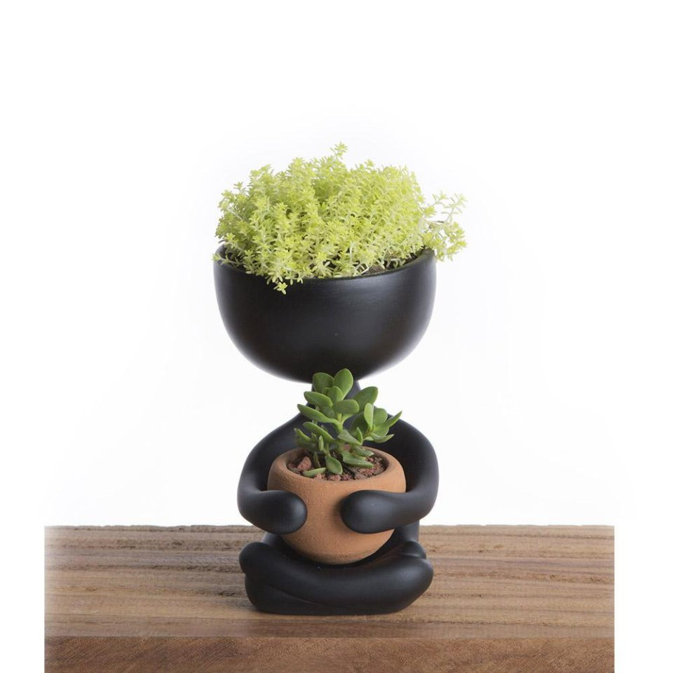 Black flowerpot in the shape of a person with plants