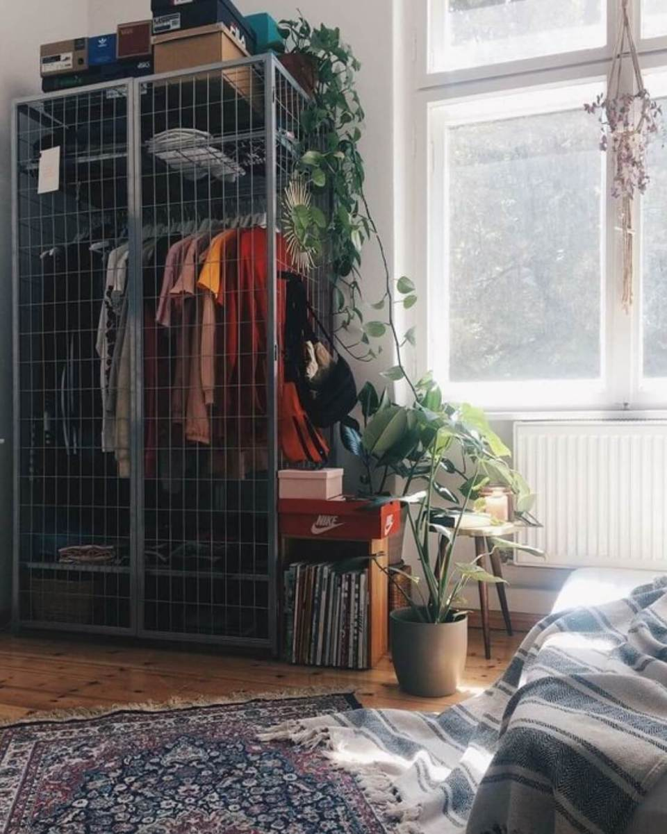 Improvised wardrobe with gray metal cage inside a room for girls