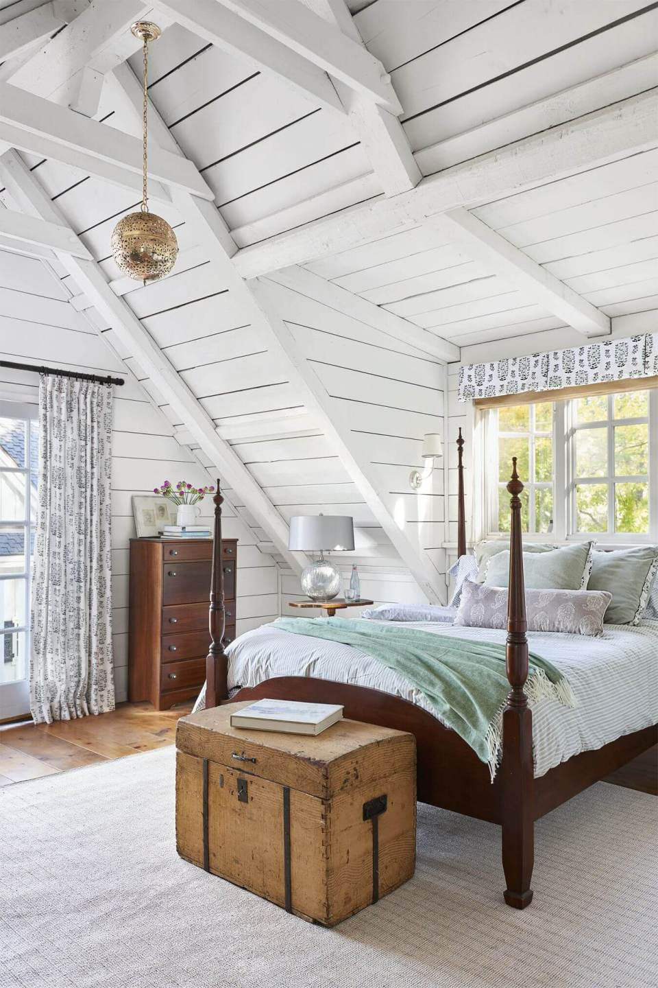 White ceilings with globe light fixture, and a vintage wood trunk