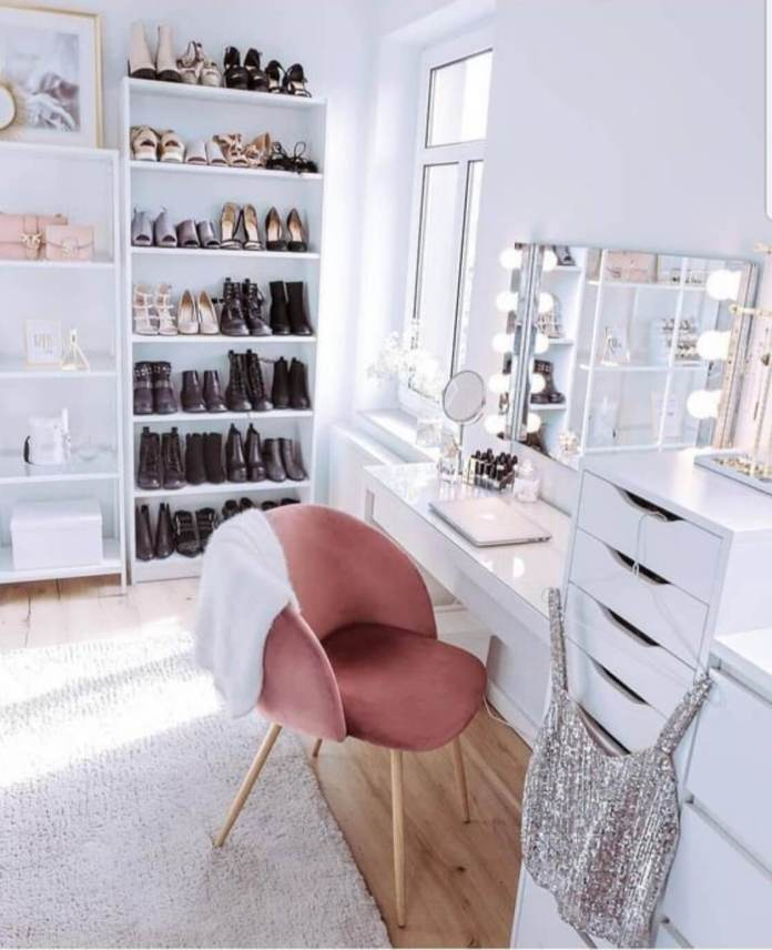 Shoeless shoe rack with dark colored boots, in front of a white dresser and a pink chair