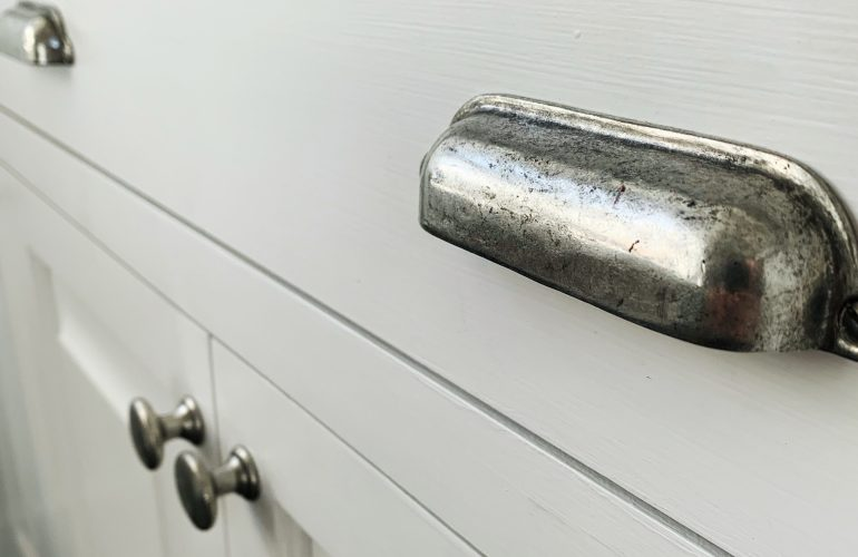 Pewter bin pulls and knobs on a farmhouse kitchen cabinet farmstandculture.com