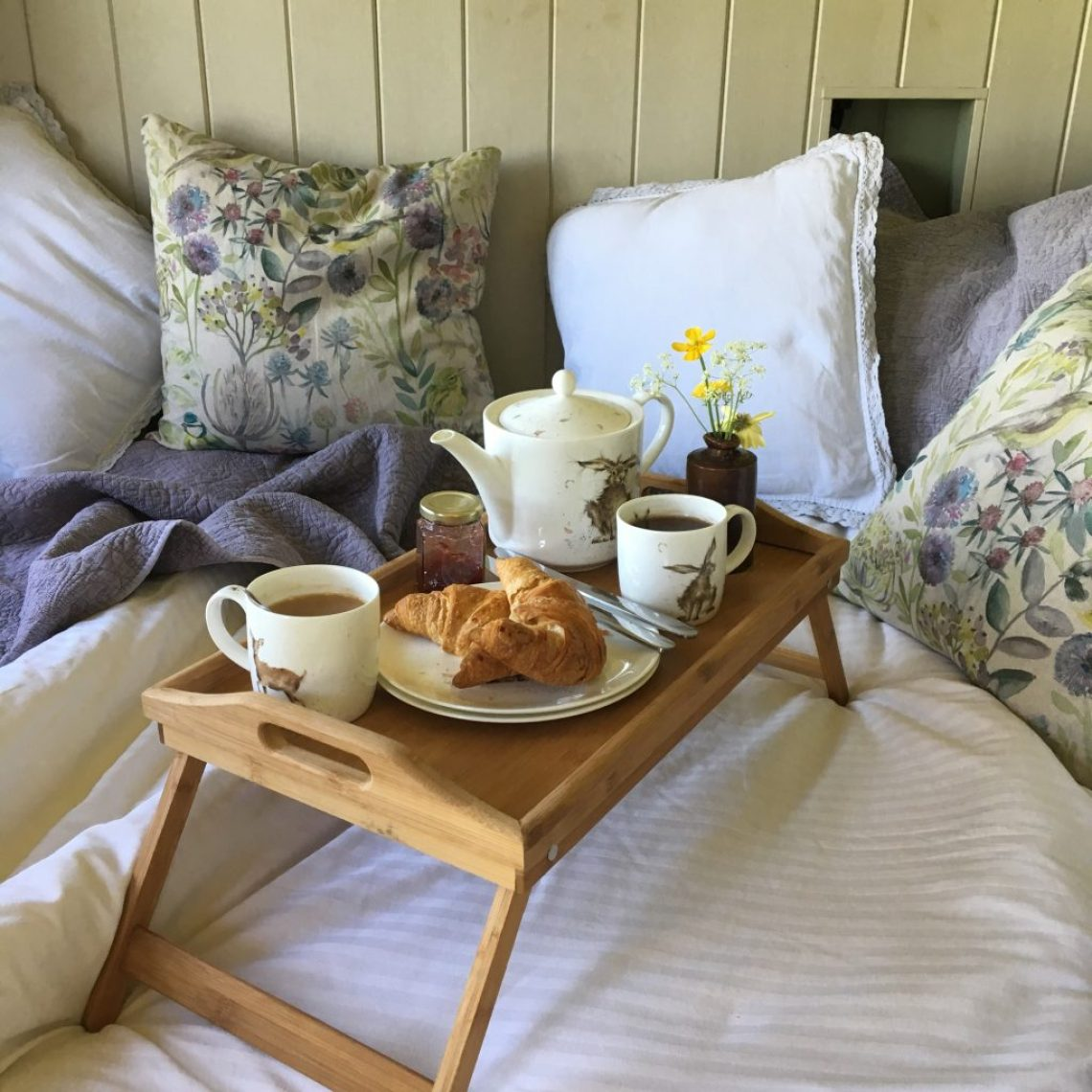 On the bed at the Happy Hare breakfast of croissants and tea sits on a tea tray
