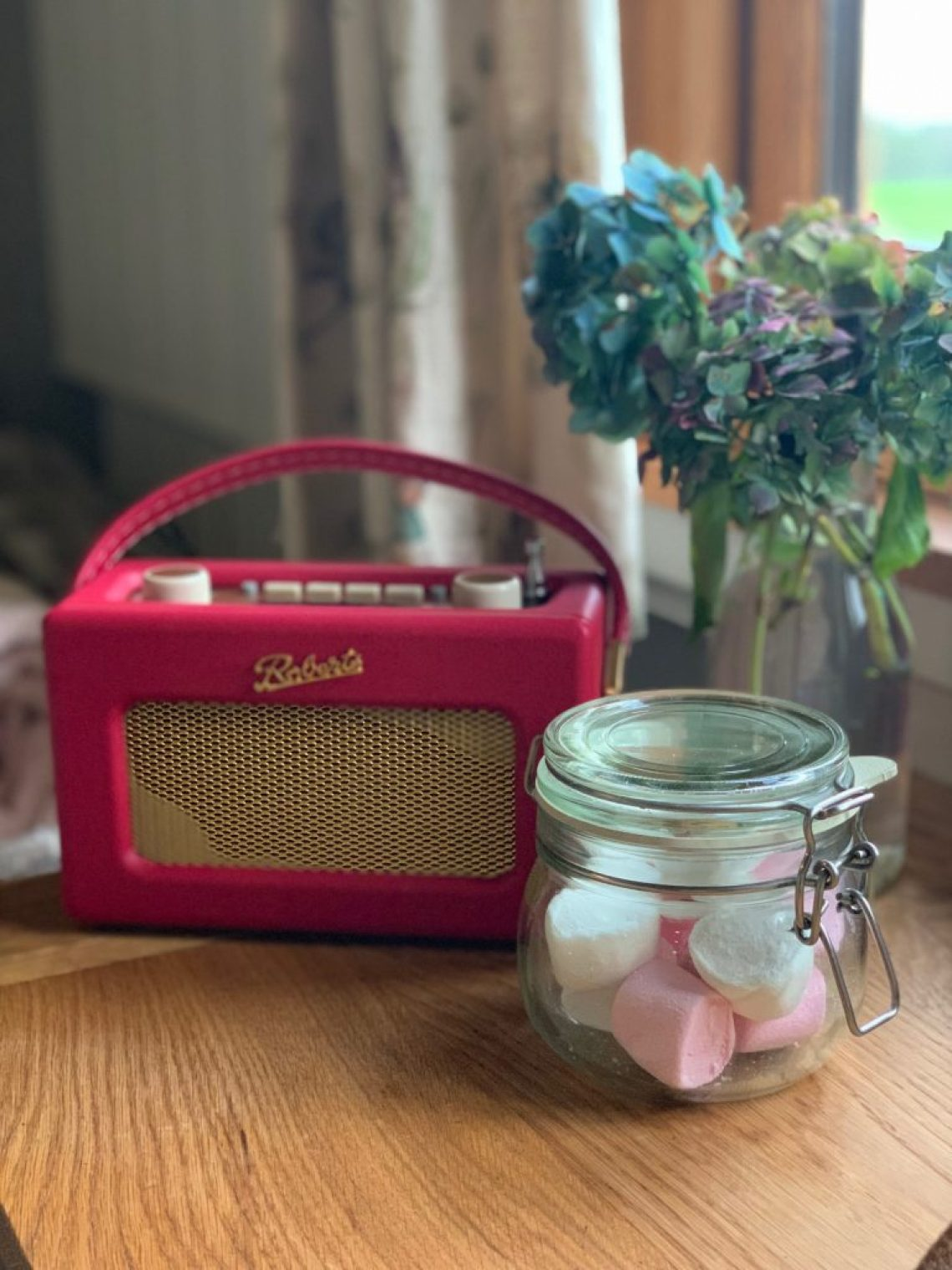 A red Roberts radio next to a bunch of hydrangeas and a jar of marshmallows