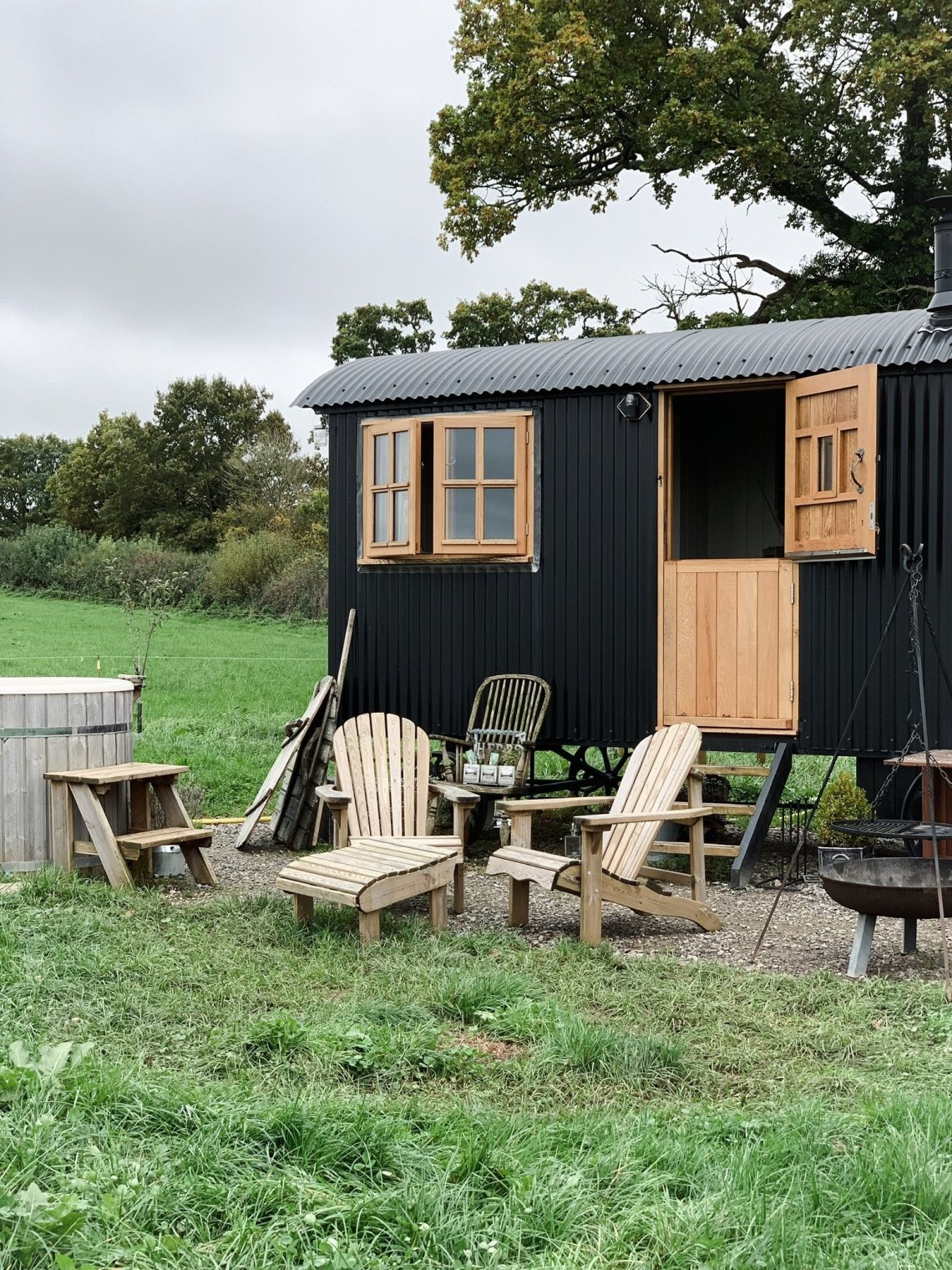 The Black Happy Hare shepherd hut with beautiful oak windows and door fire pit and Adirondack chairs