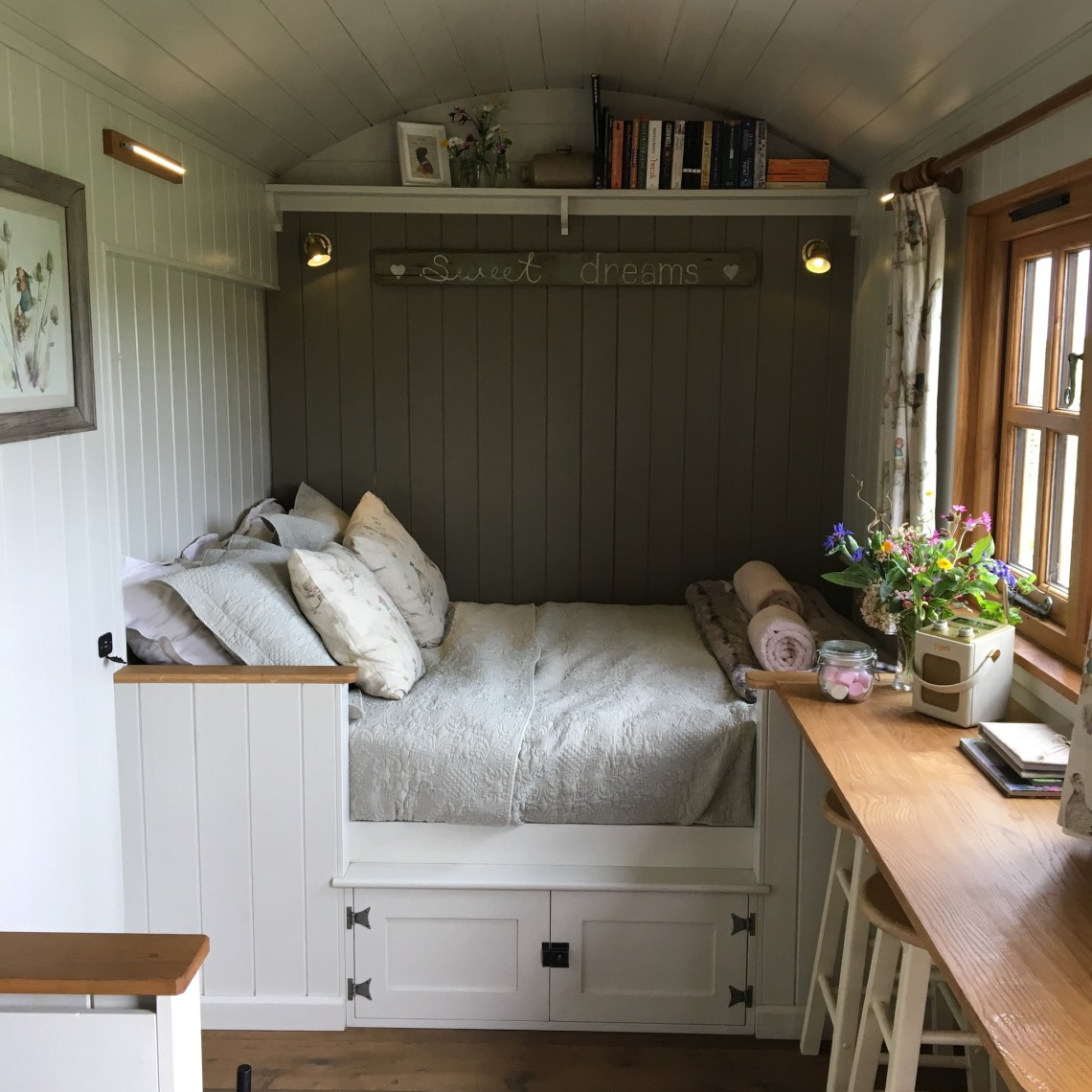 The internal layout of the pleasant pheasant shepherd hut showing a double bed made up with light green bedding and a small breakfast bar to the side
