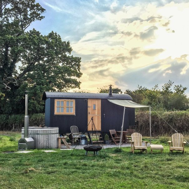 The Happy Hare shepherd huts in a field with an oak tree behind as the sun shines through from behind a cloud