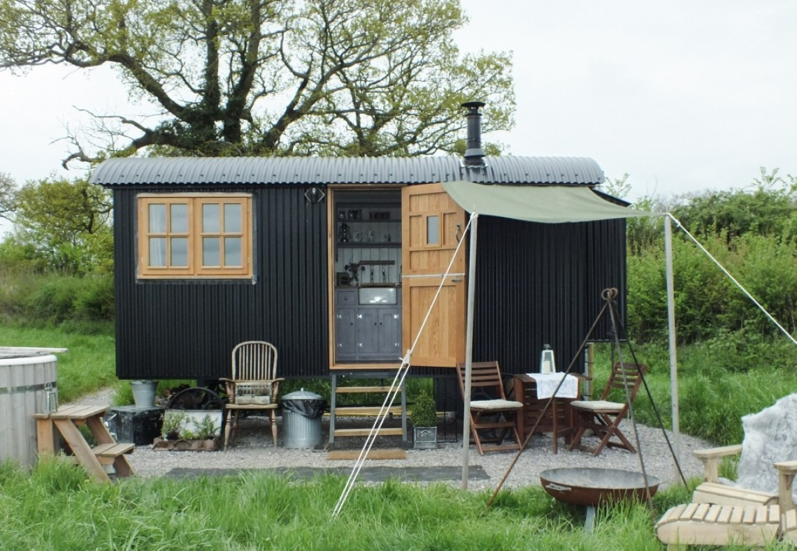 The Happy Hare is A small black shepherd hut sits in a field with table outside and a small kitchen seen through an open stable style door