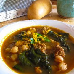 Bowl of soup with chickpeas, spinach and chorizo