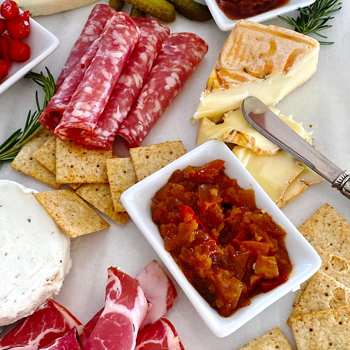 Small cheese plate with sweet red pepper chutney and charcuterie