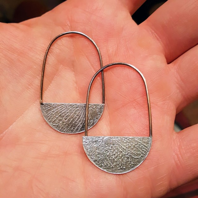 A view of the etched side of the earrings