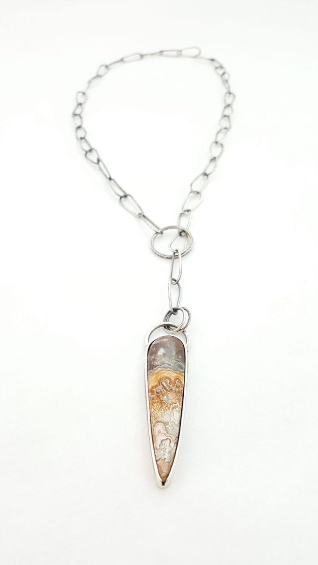 A view of the Crazy Lace and sterling silver lariat as it hangs.