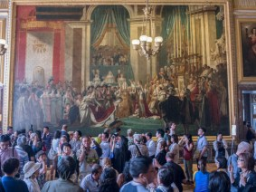 """Replica of """"The Crowning of Empress Josephine by Napoleon in Notre-Dame of Paris on 2 December 1804."""" Throngs of tourists blur make it difficult to tell where the life-sized painting begins and ends."""