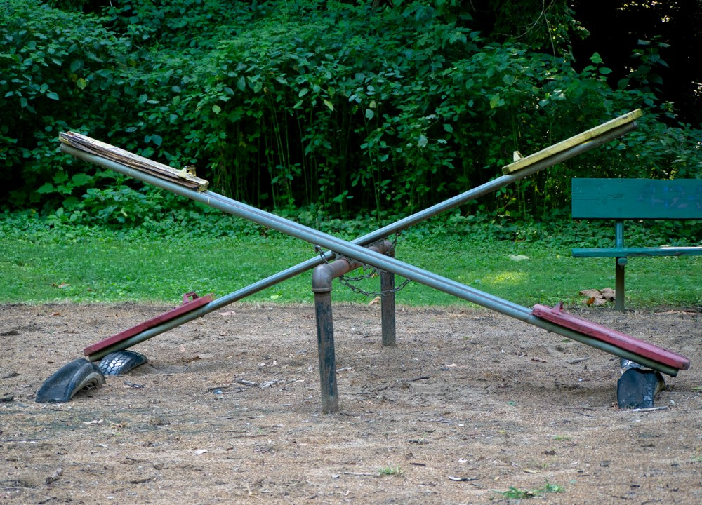 Green seesaw in small park