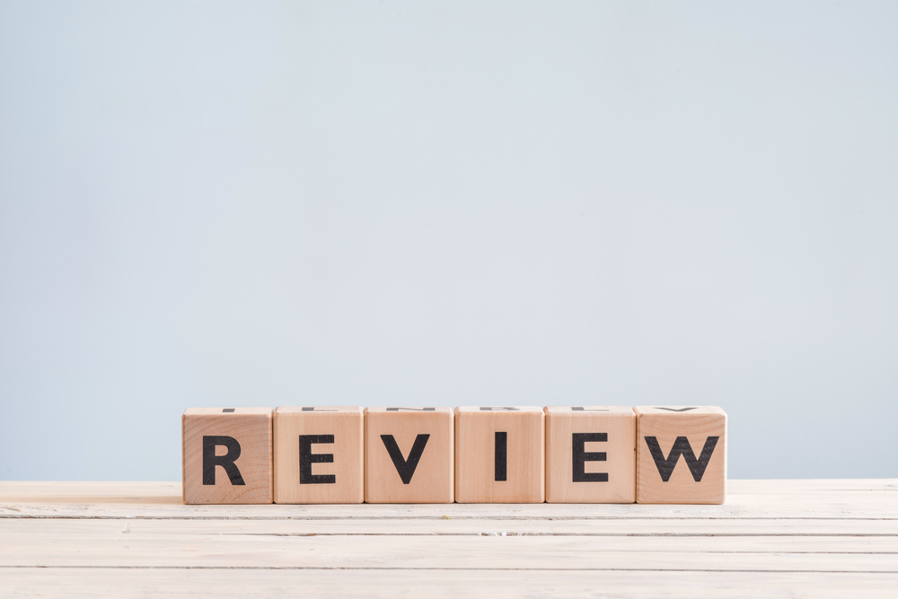 Review headline sign made of wood on a table