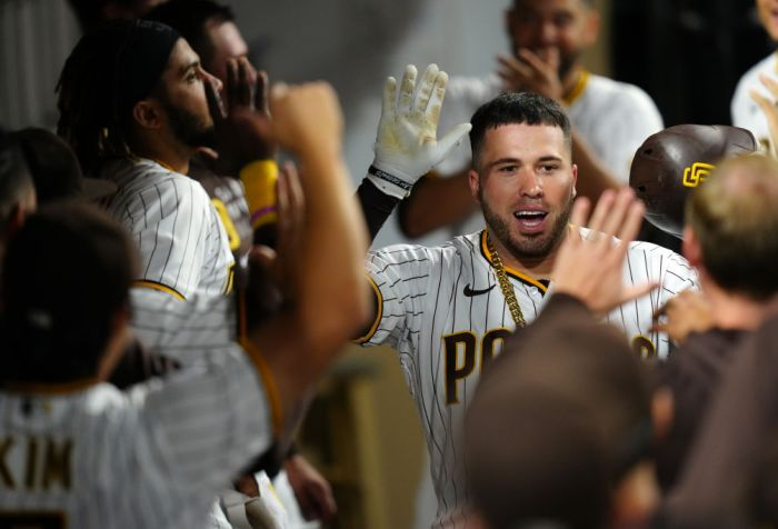 Victor Caratini, San Diego Padres catcher, high-fiving teammates in San Diego dugout