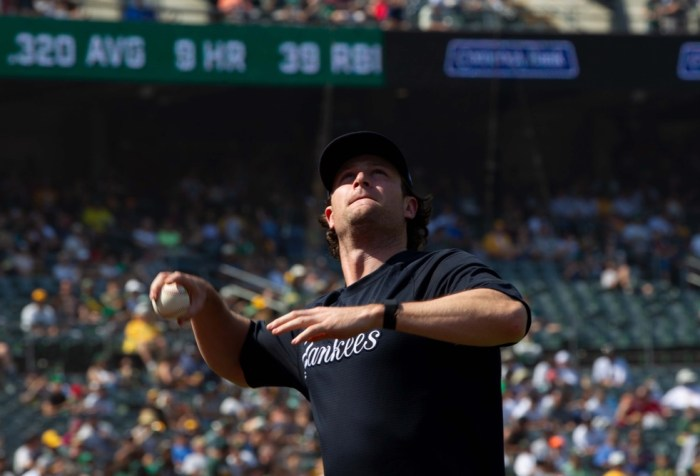 New York Yankees' Gerrit Cole throws a foul ball over the net into the stands during a game against Oakland Athletics at RingCentral Coliseum.