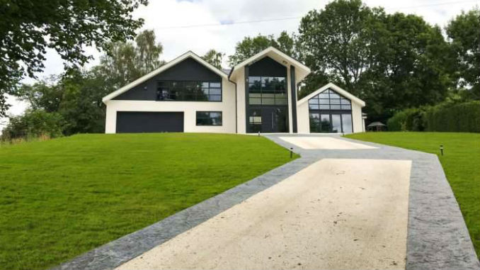 sloped resin driveway with pattern imprinted concrete border