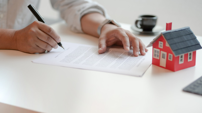 Close-up view of customer signing contract about home loan agreement