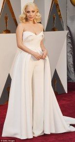 Lady Gaga in a white pantsuit with flowing train by Brandon Maxwell