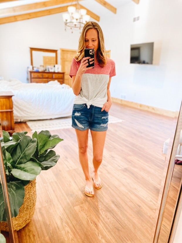 Top 7 Cute Spring Sandals for Women featured by top Pittsburgh fashion blogger, Fashionably Late Mom.  Spring Sandals by popular Pittsburgh fashion blog, Fashionably Late Mom: image of a woman wearing a woman wearing a pink and black and white stripe t-shirt , distressed shorts and white slide sandals.