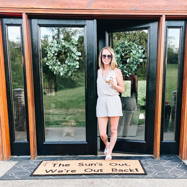 front porch decor, doormat |  Summer Front Porch by popular Pittsburg life and style blog, Fashionably Late Mom: image of a woman holding a glass of wine and standing on her front porch on a log home with black frame doors, black planters with pink flowers, hanging potted pink flower planters, and greenery wreaths.