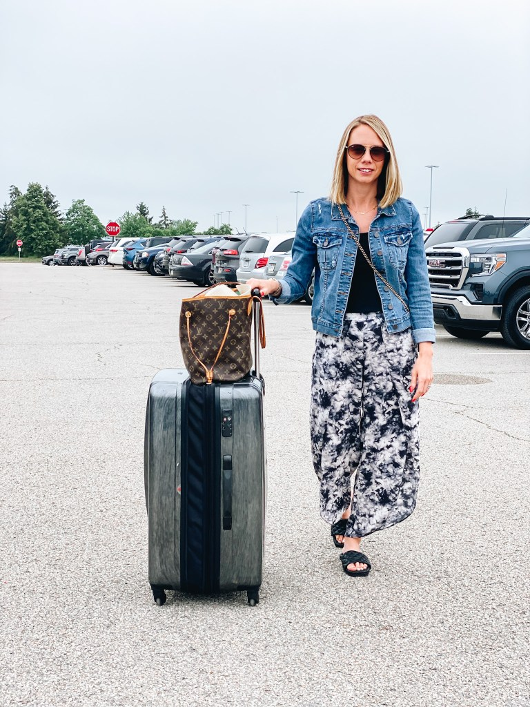 5 Top Packing Tips for your Family Vacation, featured by top Pittsburgh lifestyle blogger, Fashionably Late Mom. Packing can sometimes be stressful, but I've mastered it so it's not so bad. family vacation, luggage, how to pack, suitcase, samsonite | Packing Tips by popular Pittsburgh travel blog, Fashionably Late Mom: image of a woman wearing a denim jacket, black top, and black and white tie dye wide leg pants while pulling some rolling hard shell rolling luggage in a parking lot.