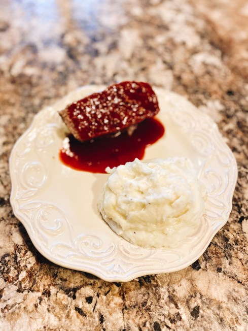 sweet and spicy meatloaf, dinner ideas, family dinner recipe, meatloaf recipe | Sweet and Spicy Meatloaf by popular Pittsburgh lifestyle blog, Fashionably Late Mom: image of a slice of meatloaf and some mashed potatoes on a white plate.