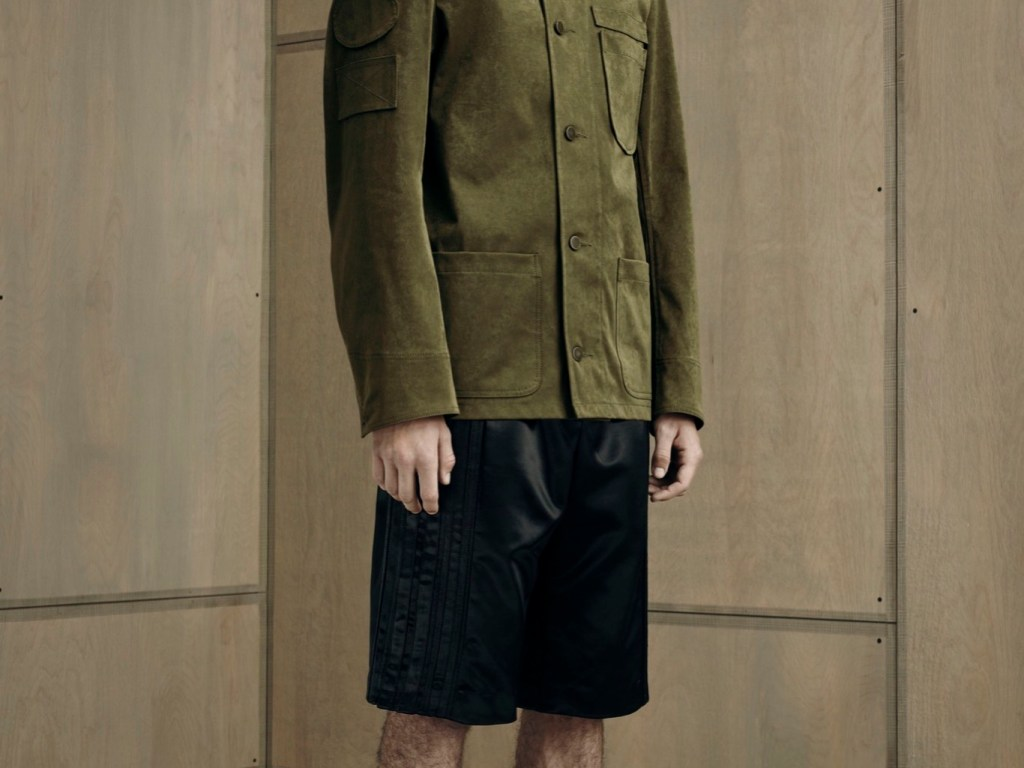 """Alexander Wang put a fresh spin on norm core for his spring collection, which took municipal uniforms as its starting point. He tweaked blue-collar staples like the mechanic's overall and plastered jackets and tops with blank leather or geometric fabric patches — a subversive spin on the name patches found on utility uniforms and Formula One pit coveralls. A leather patch embossed with an """"X"""" made for a cryptic brand marker on pants and shorts. To balance out the borderline plain cuts, Wang pushed fabric innovation. A Japanese tech knit with a peached finish gave a sculptural edge to a khaki fishtail parka, while a glossy duchesse satin elevated a bomber jacket to eveningwear status."""