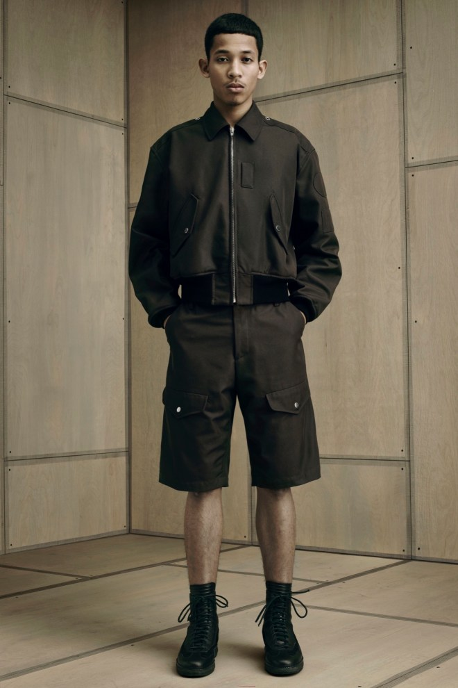 "Alexander Wang put a fresh spin on norm core for his spring collection, which took municipal uniforms as its starting point. He tweaked blue-collar staples like the mechanic's overall and plastered jackets and tops with blank leather or geometric fabric patches — a subversive spin on the name patches found on utility uniforms and Formula One pit coveralls. A leather patch embossed with an ""X"" made for a cryptic brand marker on pants and shorts. To balance out the borderline plain cuts, Wang pushed fabric innovation. A Japanese tech knit with a peached finish gave a sculptural edge to a khaki fishtail parka, while a glossy duchesse satin elevated a bomber jacket to eveningwear status."
