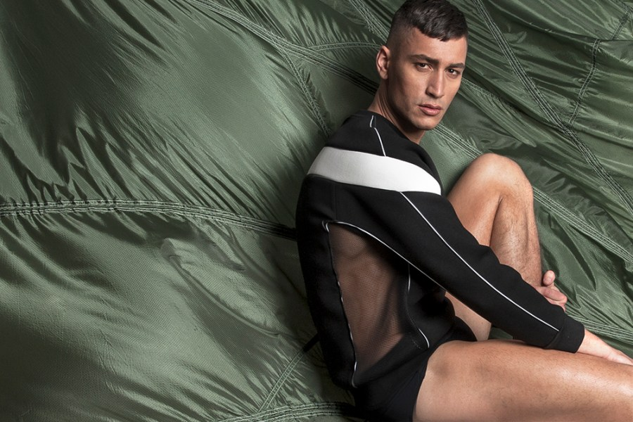"""MASS Branded's second collection titled, 'Falling Softly', brings a new sense of exhilaration, freedom and seduction to men's streetwear. Inspired by paratroopers and his memories of growing up in a military family, co-founder and designer Mass Luciano decided to create a uniform that meets the demands of the daring, active, modern man, who has a fearless sense of adventure. We like to call him, the MASS Trooper. True to MASS Branded, accentuation of the male form is essential, so the cut and the fit of the clothes – ranging from sweatpants and mesh shorts to knit sweatshirts and bomber jackets – work to broaden the shoulders, fill out the chest and slim the waist to achieve a masculine, athletic look. In accordance to this mantra, MASS Branded has taken an extra step further this collection by implementing creative, construction techniques to create parachute-like straps on the sleeveless Impact Shirt, which highlights the arms while exposing just the right amount of skin along the sides of the abdomen. After all, a man that's brave enough to jump out of a plane is a man that has no hesitation showing a little bit of skin – an idea that MASS Branded continues to tastefully execute as seen on the Assembly Sweatshirt with armour pleated panel shoulders and strategically placed mesh panels that conceal and reveal the right areas of the torso, as well as the woven Grag T-shirt with a seductive, mesh back panel. """"It was important for us to come up with innovative ways of working with mesh and high-tech fabrics, while keeping the aestheticsof a streetwear brand,"""" says co-founder Antoni d'Esterre (co-founder). Another important element of 'Falling Softly' is how easily the pieces can be paired and incorporated into your everyday wardrobe. The monochrome colours and awareness for layering transform these updated, detailed basics into long-lasting statement pieces. On top of that, the clothes have been engineered to achieve an exceptional, structured silhouette without comp"""
