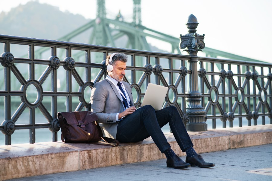Handsome mature businessman with laptop in a city. Man sitting on a bridge, using laptop and headphones.