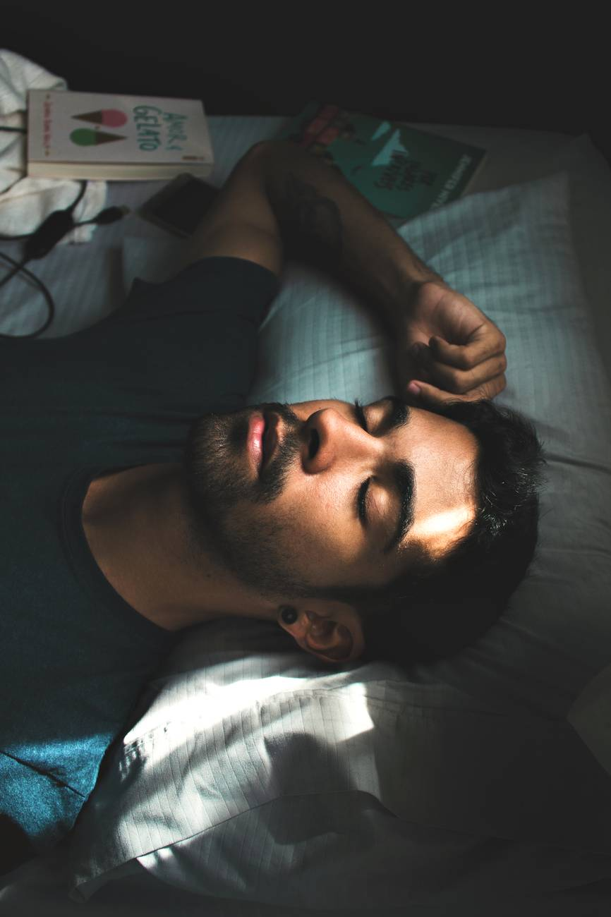man in crew neck t shirt lying on bed