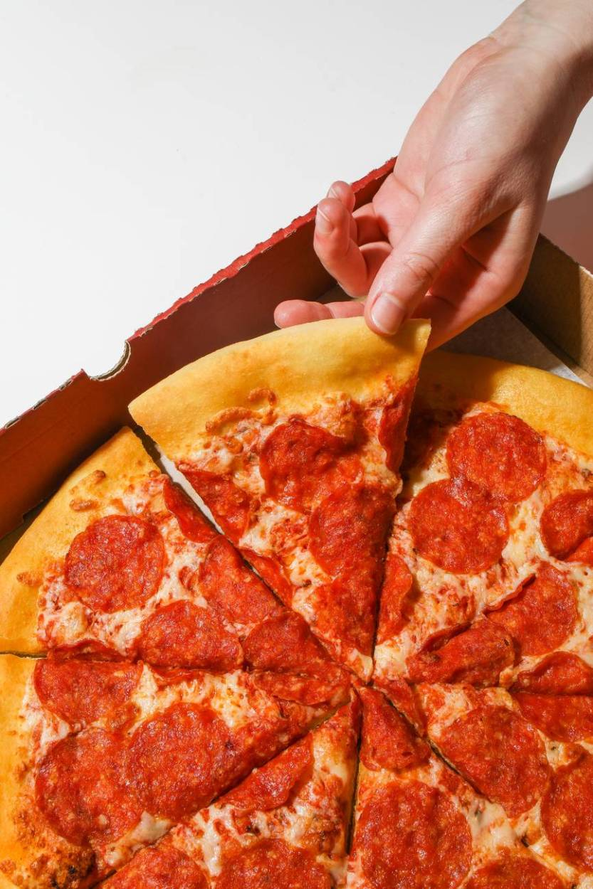 Photo by Polina Tankilevitch on Pexels.com person holding a slice of pizza