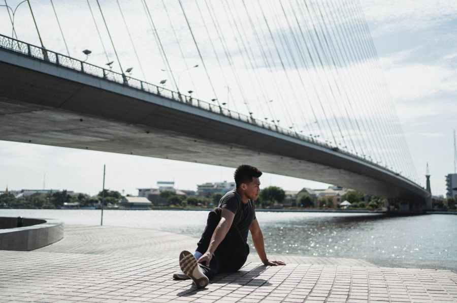 asian man sitting in sage marichi pose on city embankment