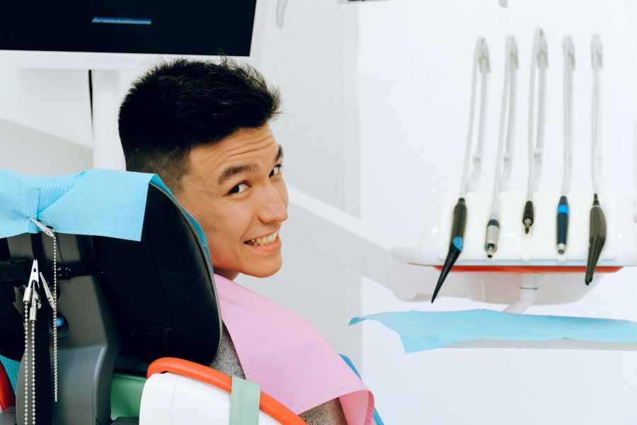 cheerful ethnic man sitting in dental chair in modern dentist office Photo by Anna Shvets on Pexels.com