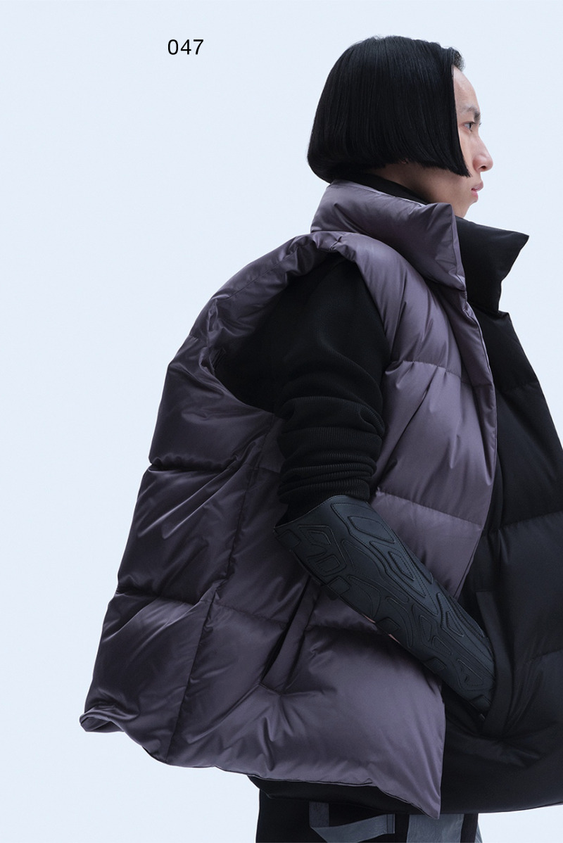 The three-dimensional pattern on the New Human one-piece helmet is derived from the AW19 version of the amphibious suit pattern and the SS21 version of the knitted totem pattern suit. Model mask as produced for the SS21 version.Mechanically pierced knitted sweater. Double-sided down vest without zipper, embroidered on the front and back with the Supernatural, Extraterrestrial & Co. logo in the same color.The robotic arm glove is the first version in its series. It evolved from the AW20 Artificial Humans concept.